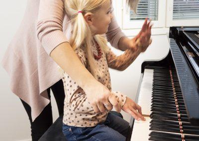 Musiikkikoulu PiaCellossa opettaja opettaa oppilaalle pianonsoittoa hauskoja tapoja käyttäen, Jyväskylä.