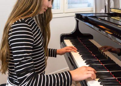 Keskittynyt pianonsoiton oppilas soittaa pianoa musiikkikoulu PiaCellossa, Jyväskylä.