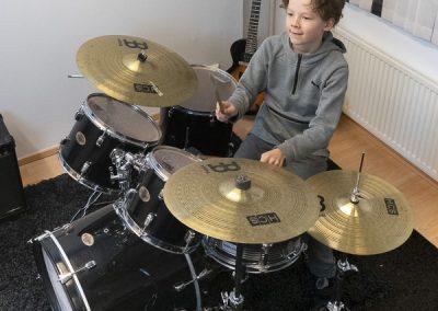 Keskittynyt nuori rumpali oppilas rumpujensoiton soittotunnilla, Jyväskylässä musiikkikoulu PiaCellossa.