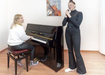 Musiikkikoulu PiaCellon laulu ja pianotunnilla sisarus oppilaat soittamassa pianoa ja laulamassa, Jyväskylä.