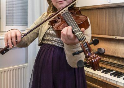 Musiikkikoulu PiaCellon viulunsoiton oppilas näyttää oikean viulunsoiton asennon, Jyväskylä.